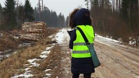 Empleado de sexo femenino de la silvicultura en el camino forestal mojado en invierno almacen de metraje de vídeo