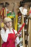 Empleado de sexo femenino mayor que sostiene la herramienta que cultiva un huerto mientras que usa el teléfono móvil Foto de archivo