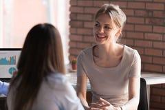 Empleado de sexo femenino sonriente que tiene charla amistosa con los colegas foto de archivo libre de regalías