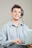 Empleado de sexo masculino del centro de atención telefónica que usa el ordenador portátil Imagenes de archivo