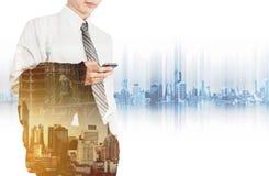 Empleado del negocio que usa el teléfono elegante con la ciudad de la exposición doble en salida del sol y la construcción del si Imágenes de archivo libres de regalías