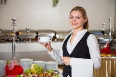 Empleado del servicio del abastecimiento en el restaurante que presenta con el plato de sopa Imagen de archivo libre de regalías