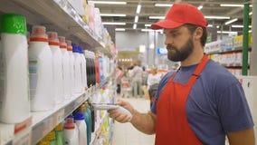 Empleado del supermercado en código de barras de los limpiadores de la exploración del uniforme del rojo en tienda al por menor m metrajes