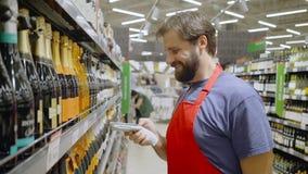 Empleado del supermercado en código de barras rojo de la exploración del aport en la sección del vino en supermercado almacen de video