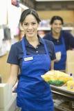 Empleado del supermercado en delantal azul fotos de archivo