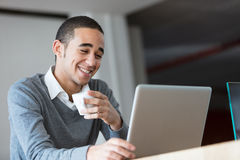 Empleado feliz con café y el ordenador portátil Imágenes de archivo libres de regalías