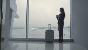 Empleado hermoso del aeropuerto cerca de la ventana en el pasillo metrajes