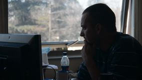 Empleado joven que mira el monitor de computadora almacen de video
