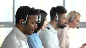 Empleado negro en centro de atención telefónica y compañeros de trabajo detrás