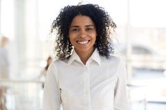 Empleado o interno africano joven sonriente de mujer en portrai de la oficina imagenes de archivo