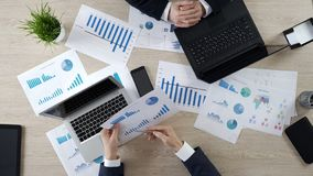 Empleado que muestra estadísticas a su colega, compartiendo opiniones, visión superior fotografía de archivo libre de regalías