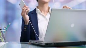 Empleado sonriente feliz de la señora que escucha la música en los auriculares, relajándose en rotura almacen de metraje de vídeo