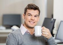 Empleado sonriente que come café en centro de atención telefónica Fotografía de archivo libre de regalías