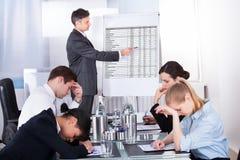 Empleados aburridos en la reunión de negocios imagenes de archivo
