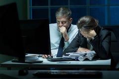 Empleados con exceso de trabajo que trabajan en la noche imagenes de archivo