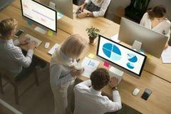 Empleados corporativos que trabajan en los ordenadores en oficina junto, top imagen de archivo