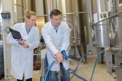 Empleados de la cervecería que limpian el piso imágenes de archivo libres de regalías