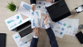 Empleados de la compañía que discuten estadísticas juntas, compartiendo opiniones, visión superior imagen de archivo libre de regalías