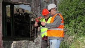 Empleados de la construcción que hablan cerca del edificio dañado almacen de metraje de vídeo