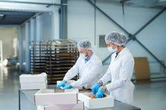 Empleados de la fábrica de la confitería que embalan los pasteles en las cajas fotos de archivo libres de regalías