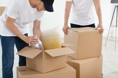 Empleados de mudanza del servicio con las cajas de cartón y pertenencia en sitio fotos de archivo