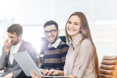 Empleados del ` s de la compañía con un ordenador portátil que se sienta en el pasillo de la oficina moderna imagen de archivo