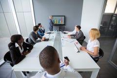 Empleados en la sala de reunión escuchar director imagen de archivo