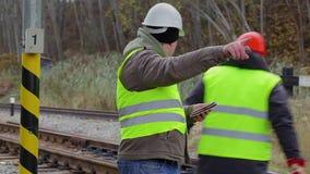 Empleados ferroviarios con la tableta y la llave ajustable almacen de metraje de vídeo