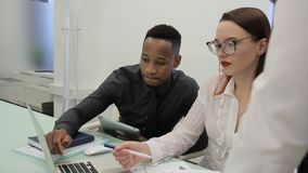 Empleados jovenes que trabajan en el escritorio usando el ordenador portátil en oficina moderna metrajes