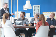 Empleados que escuchan su encargado imagenes de archivo