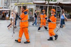 Empleados que limpian la compañía en el funcionamiento anaranjado en la calle imagen de archivo