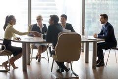 Empleados que sacuden las manos en la negociación del negocio en oficina imagenes de archivo