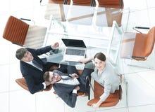 Empleados que se sientan en el escritorio y que miran para arriba Imágenes de archivo libres de regalías