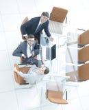 Empleados que se sientan en el escritorio y que miran para arriba Imagen de archivo