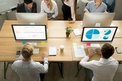 Empleados que usan los ordenadores que trabajan con el personal en la oficina, visión superior foto de archivo libre de regalías