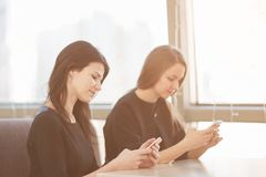 Empleados que usan sus smartphones que se sientan en una tabla en un caf? imagen de archivo