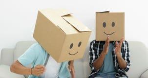 Empleados tontos con las cajas en sus cabezas que hacen el robot almacen de metraje de vídeo