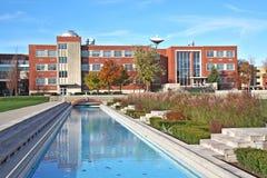 Empleando y piscina de reflejo un campu de la universidad Foto de archivo