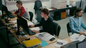Emploees está trabajando en la oficina del espacio abierto en el escritorio común con los ordenadores metrajes