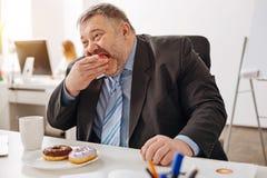 Employé affamé corpulent mordant un morceau d'un beignet images libres de droits