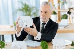 Employé attentif évaluant la miniature d'une bonne maison Photo libre de droits
