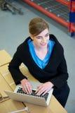 Employé d'entrepôt dactylographiant sur l'ordinateur portable Photographie stock libre de droits