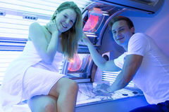 Employé dans un solarium conseillant le client ou le client au lit de bronzage Image libre de droits