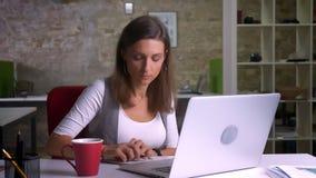 Employé de bureau attirant s'asseyant devant l'ordinateur portable et prenant des notes buvant le cofee sur le lieu de travail à  banque de vidéos