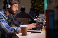 Employé de bureau avec du café au bureau travaillant tard sur l'ordinateur portable Photographie stock libre de droits