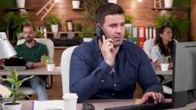 Employé de bureau ayant une conversation téléphonique dans le bureau moderne et confortable banque de vidéos