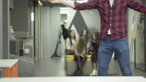 Employé de bureau barbu montant un vélo sur le bureau Un homme démantèle sa position de collègue avec des papiers dans le lieu de banque de vidéos