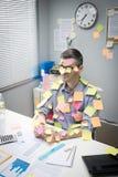 Employé de bureau couvert de notes de bâton Image libre de droits