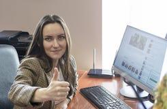 Employé de bureau de fille d'amusement montrant des pouces se reposant à l'ordinateur au travail Image stock