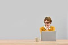 Employé de bureau de fille devant l'ordinateur portable Image libre de droits